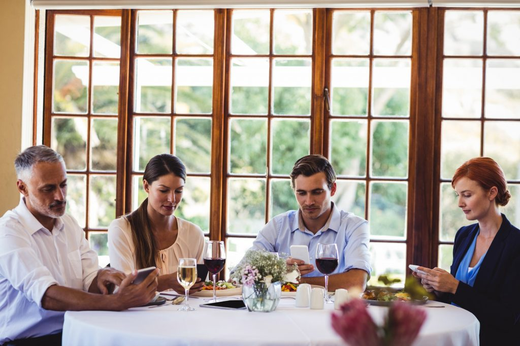 Business people using mobile phone at table
